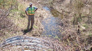 A road technician examines a culvert conveying Potash Brook beneath Interstate 89 in South Burlington in this undated photo.