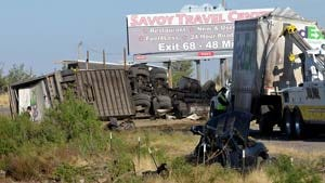 A dark pickup truck lies in the bottom foreground on June 22, 2011, along westbound Interstate 10, mile marker 117, after it was involved in an impact with a FedEx tractor-trailer resulting in multiple fatalities, including the driver of the semi-truck.