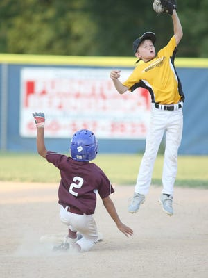 Einspahr Construction's Quincy Hobbs beats the throw to second while Bradley Automotive shortstop Noah Hackman goes in the air for the ball in the fourth inning Tuesday night in Cal Ripken Minor at the Cooper County Baseball Association ballfield.