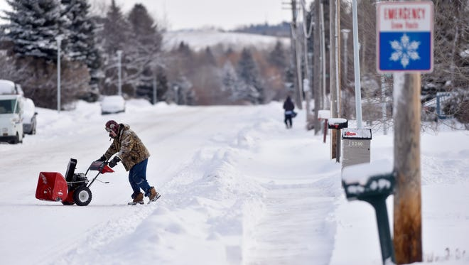 Leroy Meddock heads for his garage after plowing his neighbor's sidewalk in the Park Garden area in Great Falls last winter. It won't be a white Christmas this year in Great Falls, where Christmas Day can be balmy or below zero depending on the year.