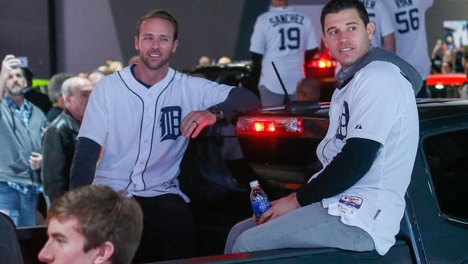 Ian Kinsler, right, rides in a car parade with Andrew Romine as the Tigers' winter caravan visits the the North American International Auto Show.