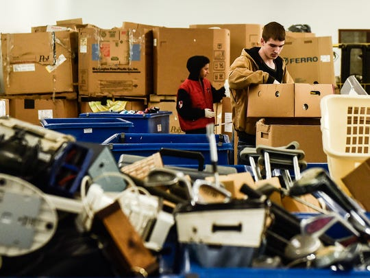 Goodwill employees, many from Rushmore Academy, sort