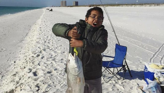 Local angler Davi Vieira with a nice over slot redfish he caught fishing on Pensacola Beach with his dad.
