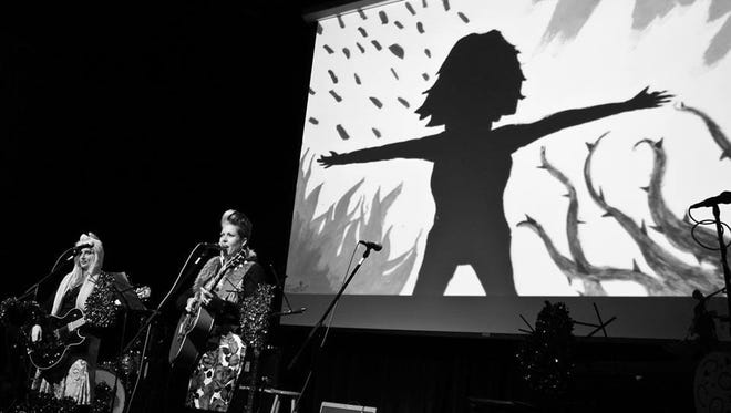 """Liv Mueller, left, and Ruby James perform the song """"Superpowers"""" with the artwork used to inspire the freshly written song, """"Envy"""" by Eleanor Knippel, projected above them on stage at one of last year's """"Love on Holiday"""" concerts at Third Avenue Playhouse."""