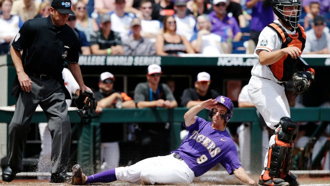 LSU's Zach Watson (9) slides past Oregon's catcher Adley Rutschman (35) to score on a sacrifice bunt by Beau Jordan during the second inning of an NCAA College World Series baseball game in Omaha, Neb., Friday, June 23, 2017.
