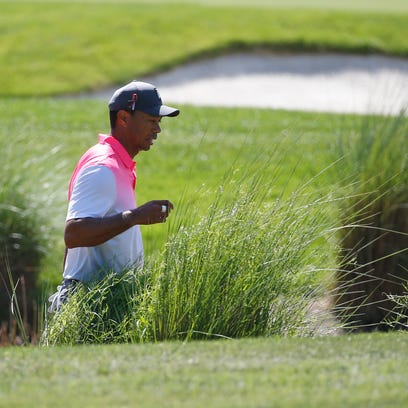 Tiger Woods looks for his ball in the tall grass on the second hole during the second round of the Honda Classic golf tournament, Friday, Feb. 23, 2018, in Palm Beach Gardens, Fla. (AP Photo/Wilfredo Lee)