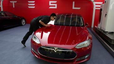 A worker cleans a Tesla Model S sedan in this file photo. The company could announce the location of its gigafactory sometime today.