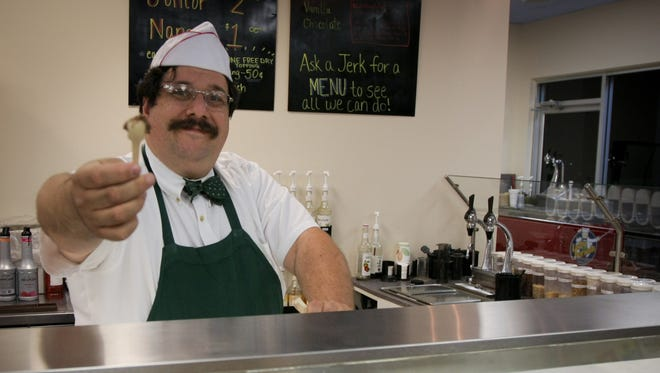 Owner Greg Cohen stands behind the counter of Lofty Pursuits in Tallahassee, Florida.