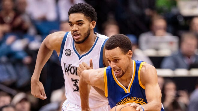 Golden State Warriors guard Stephen Curry dribbles in the first quarter against  Minnesota Timberwolves center Karl-Anthony Towns.