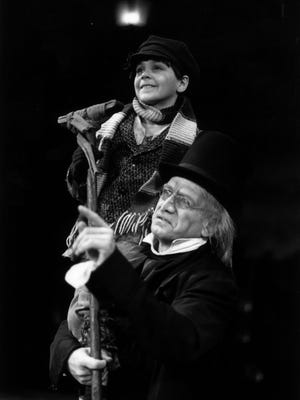 """Daniel Mooney, playing Scrooge, hoists Teddy Anagnostopoulos, playing Tiny Tim, in the 1989 Milwaukee Repertory Theater production of """"A Christmas Carol."""" Teddy's nephew, also named Teddy Anagnostopoulos, performs in the Rep's 2017 production of """"A Christmas Carol."""""""