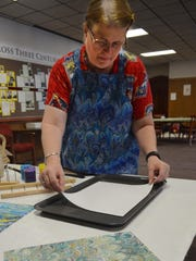 Annie Tremmel Wilcox lays paper in water as she demonstrates