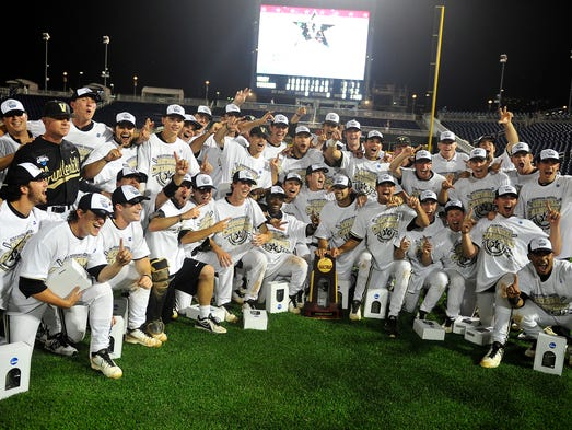 Vanderbilt coaches and players have their team photo taken with a trophy after defeating Virginia 3-2 at the College World Series at TD Ameritrade Park in Omaha, Neb., Wednesday, June 25, 2014.