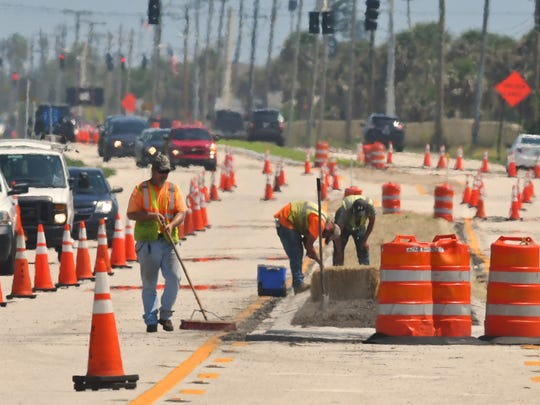 Heat waves shimmering off of Highway A1A on Tuesday afternoon, as workers from a State road crew brave the broiling heat  in Satellite Beach.