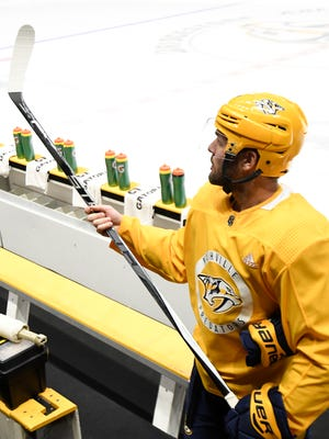 Predators center Mike Fisher checks his stick before taking the ice at a morning practice Monday at Bridgestone Arena.