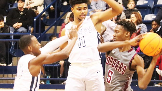 Shawnee's Karran Evans (left) and J'Briell Easley (11) apply defensive pressure to Ada's Jaxson Robinson (5) when the two teams met on Dec. 20 in Shawnee. The two teams will do battle again tonight in Ada.