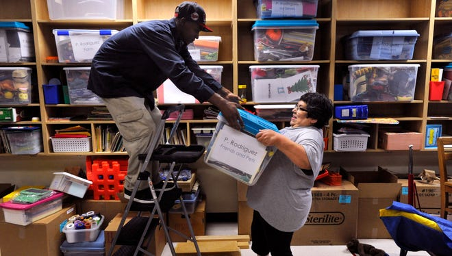 Henry Brown assists Patsy Rodriguez with lifting a plastic bin onto a shelf in her new classroom at Long Early Learning Center Wednesday July 26, 2017. Rodriguez has been a teacher for 35 years at AISD, moving into her new classroom required to say goodbye to some of the things she'd accumulated in that time. Even so, she admitted she still had quite a bit to organize before school starts Aug. 28.