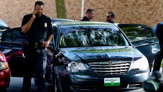 Police investigate at the scene where a stolen car