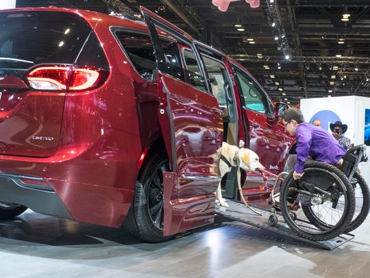 Mork, a companion dog for  Wallis Brozman, a spokesperson for Canine Companions for Independence, demonstrates how Mork provides assistance by pulling up her wheelchair into the Chrysler Pacifica / Braun Automobility van at the Chicago Auto Show on Feb. 9, 2017.