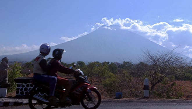 Motorists ride past by with Mount Agung volcano seen in the background in Karangasem, Bali, Indonesia, Thursday, Sept. 28, 2017.