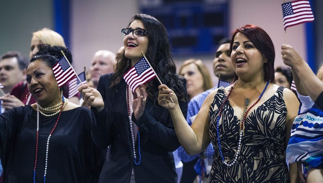 "Immigrants sing ""God Bless The USA"" during a U.S. Citizenship and Immigration Services ceremony at South Mountain Community College, Friday, July 23, 2015."