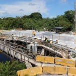 A construction crew works on the Chalan Santo Papa Juan Pablo Dos Bridge in Hagatna on Aug. 31. The completion date of the project has changed a few times since work began in June 2014. It is now scheduled to be complete in October.