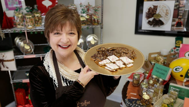 Karen Peltier, founder of KP! Toffee in Sturtevant, holds an assortment of toffee at the company's new store, where they also make all of their toffee and confections.