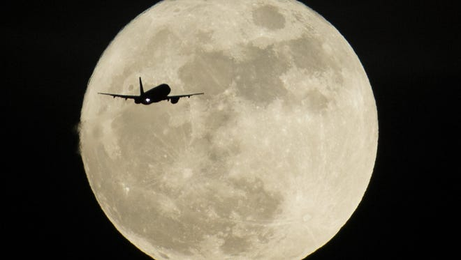 A plane crosses in front of a rising supermoon in Mesa on Dec. 13, 2016.