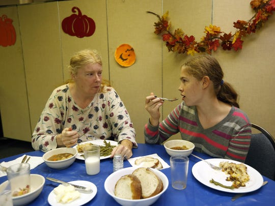 Vicki McMahon, left, and her daughter, Cheyennee McMahon-Dumont, dine on venison at a church dinner in Portland, Maine.
