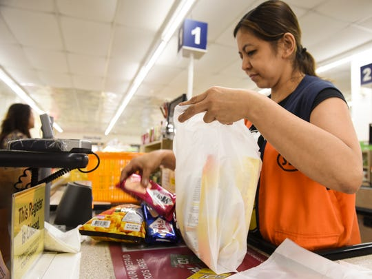 Cashier, Beth Magdey, places bought goods into a plastic shopping bag for a customer at the California Mart in Tamuning on Friday, May 4, 2018.