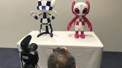 "In this Thursday, July 18, 2019, photo, a journalist takes a photo of robots of mascots of Olympics ""Miraitowa,"" left, and Paralympics ""Someity"" shown at Toyota Motor Corp. headquarters in Tokyo. The mascot robots' eyes change to the images of stars and hearts. The Japanese automaker Toyota, a major Olympic sponsor, is readying various robots for next year's Tokyo Olympics. (AP Photo/Yuri Kageyama)"