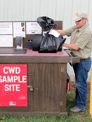 Tim Lizotte with the Wisconsin DNR checks a kiosk at Kettle Moraine State Forest in Eagle last year that allowed hunters to deposit deer samples for CWD testing.