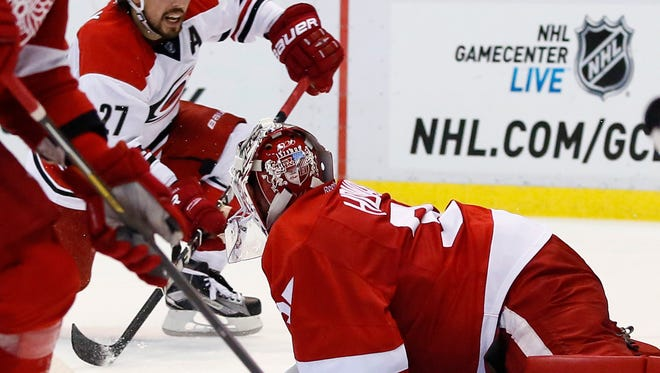 The Hurricanes' Justin Faulk scores against Red Wings goalie Jimmy Howard (35) during the second period of the Wings' 5-3 loss Friday at Joe Louis Arena.