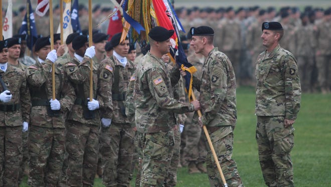 Outgoing 3rd Brigade Combat Team commander Col. J.B. Vowell, right, observes as Maj. Gen. Gary J. Volesky, commanding general of the 101st Airborne Division, passes the guidon to incoming 3rd BCT commander Col. Larry Q. Burris Jr. on Friday at Fort Campbell's Division Parade Field.