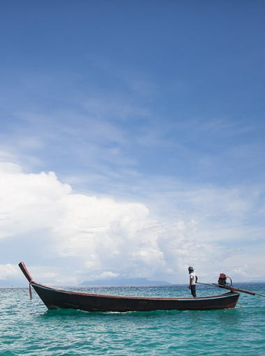 A driver steers his longboat in the Andaman Sea off the shore of Ko Lipe, Thailand.