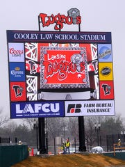 Workers are busy around the new Lansing Lugnuts scoreboard