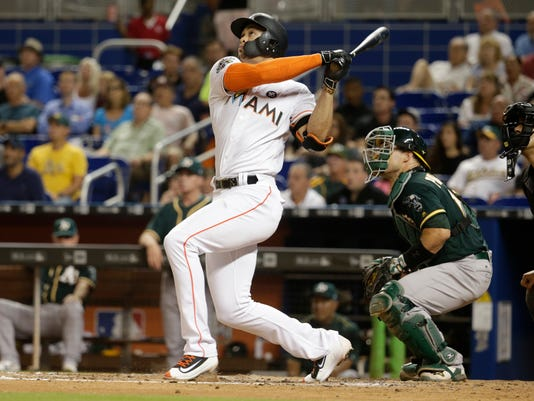 Miami Marlins' Giancarlo Stanton, left, watches after hitting a two-run home run during the fifth inning of an interleague baseball game against the Oakland Athletics, Tuesday, June 13, 2017, in Miami. At right is Oakland Athletics catcher Josh Phegley. (AP Photo/Lynne Sladky)