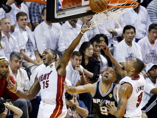 Miami Heat guard Mario Chalmers (15) blocks a shot to the basket by San Antonio Spurs guard Tony Parker (9) as Miami Heat forward Rashard Lewis (9) defends, during the second half in Game 3 of the NBA basketball finals, Tuesday, June 10, 2014, in Miami. (AP Photo/Lynne Sladky)