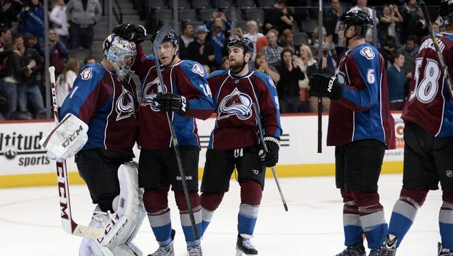 Colorado Avalanche goalie Semyon Varlamov (1) is congratulated for the win by right wing Marc-Andre Cliche (24) and center Ryan O'Reilly (90) and defenseman Erik Johnson (6) against the Carolina Hurricanes at Pepsi Center.