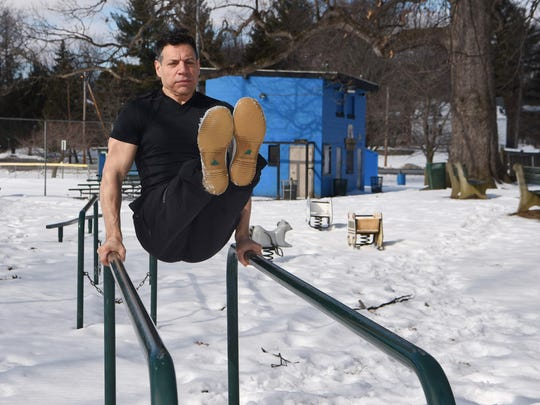 Michael Polito performs an L-sit on the parallel bars