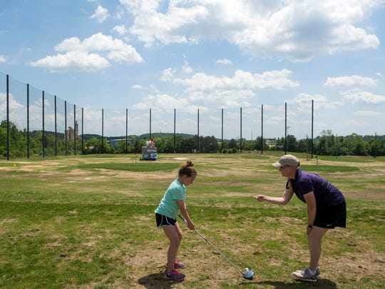 Lindy McGuire, program director at First Tee of Greater Knoxville and LPGA golf instructor, helps Kyndal Wolfenbarger with her gold drive at the Food City Kid's Clinic at Fairways and Greens on Sunday, May 6, 2018. Kyndal is on the golf team at Alcoa Middle School.