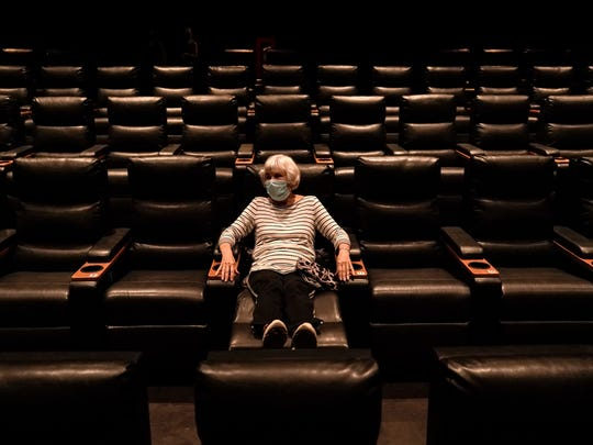 Karen Speros, 82, waits for a movie to start at a Regal movie theater in Irvine, Calif., on Tuesday. Gov. Gavin Newsom relaxed coronavirus restrictions in five more counties, clearing the way for restaurants, movie theaters, gyms, and churches to resume indoor activities with fewer people and other modifications.
