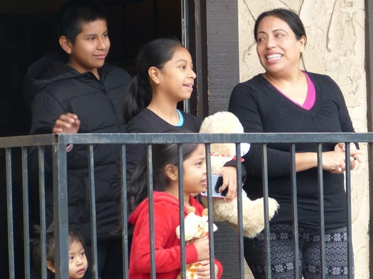 """Maria Calles and her children, Fabian, 11, Isabella, 9, Andrea, 4, and Emma, 1, were all smiles after """"Blue"""" Santa Claus paid them a visit at their Churn Creek Road apartment."""