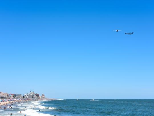 A plane flying an advertisement banner flies over Ocean City beach on Monday.