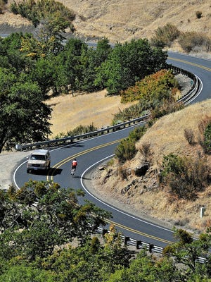 A bicyclist rides down Dead Indian Memorial Road near Ashland, Ore.