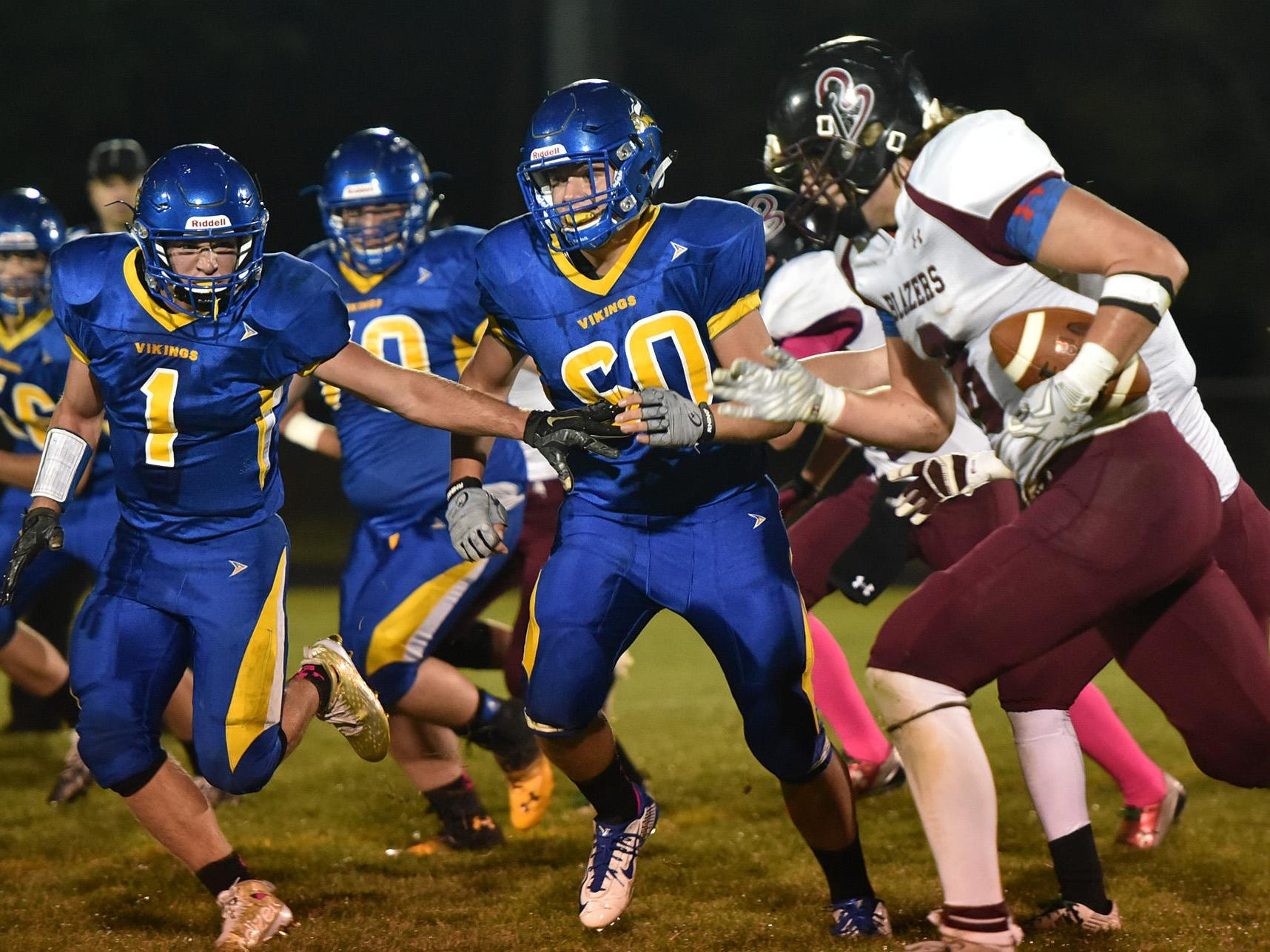 Gibraltar's Logan Ferry (1) and Nathan Ewaskowitz (60) attempt to get to N.E.W. Lutheran running back Gabe Lloyd during the 8-man football game Friday night. NEW moved to 8-0 with a 42-24 win.