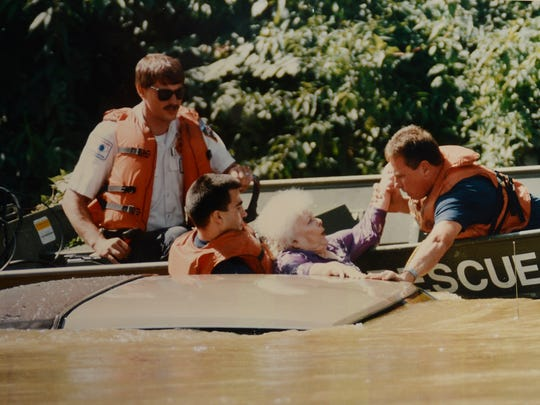Two Asheville High classmates, Steve Friedl, left, and Joe Meadows, rescue a woman whose car was swept from Swannanoa River Road into the river by floodwaters.<252>