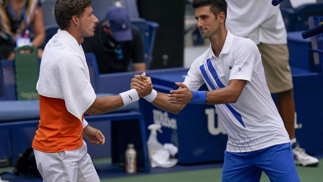 Novak Djokovic, of Serbia, shakes hands with Pablo Carreno Busta, of Spain, after defaulting the match during the fourth round of the US Open tennis championships, Sunday, Sept. 6, 2020, in New York. Djokovic inadvertently hit a line judge with a ball after hitting the ball in reaction to losing a point to Carreno Busta.