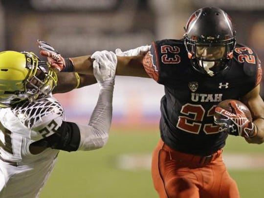 Oregon linebacker Derrick Malone (22) attempts to make a tackle as Utah running back Devontae Booker (23) carries the ball in the second quarter during an NCAA college football game Nov. 8, 2014, in Salt Lake City.