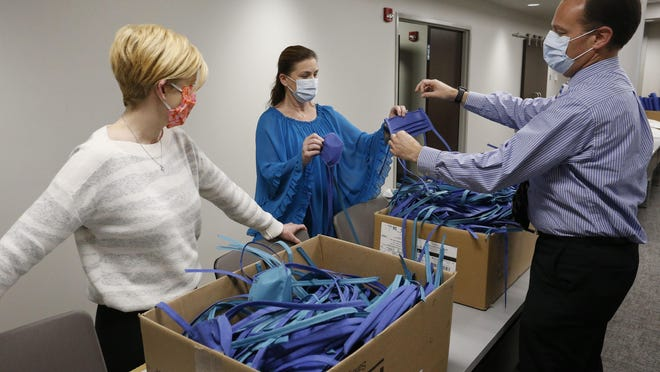 Jeanette Waterman and Jackie Betz volunteers at the DCH Foundation office, show completed masks to Andy North that are ready to be delivered to the hospital for use Friday, April 10, 2020.