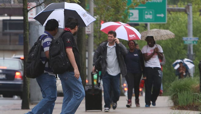 People walk along Hamilton Avenue in downtown White Plains during light rainfall  May 16, 2014.